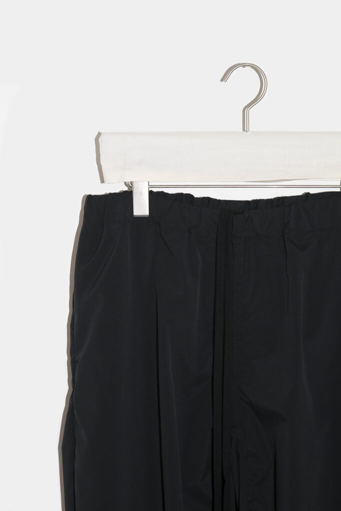 YOKO SAKAMOTO 21AW UTILITY TRACK PANTS ミリタリーのトレーニングパンツを彷彿させるユーティリティートラックパンツ。前身頃から後身頃にかけて、サイドに切替が無い一枚続きのノーシームパターンを採用した賛沢な仕様です。家庭でガシガシ洗濯出来る様に耐久性の強い生地を選びました。気軽に普段使いが出来て、履けば履くほど経年変化も楽しめます。ベルトループ、ウエスト紐付きで、様々なサイズ感に対応可能です。